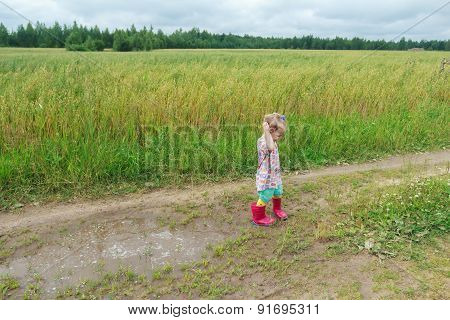 Two Years Old Preschooler Girl Playing On Farm Dirt Road Near Puddle