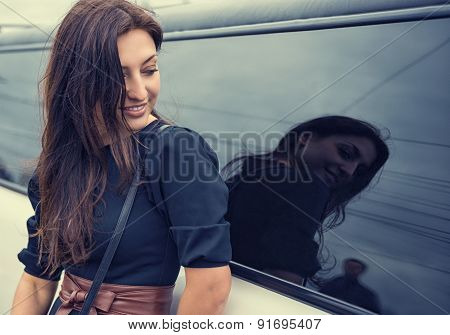 Beautiful young woman looking at the man in the reflection of automotive glass.
