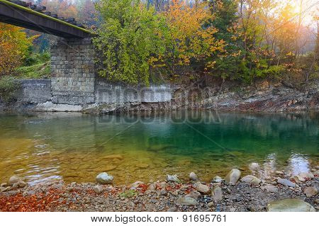 Mountain River And Railway Bridge In Autumn At Sunset