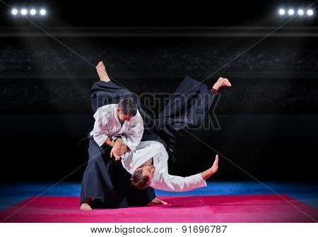Fight between two martial arts fighters at sports hall