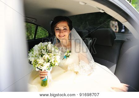 Young Pretty Smiling Bride With Bouquet Sitting On The Car