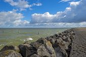 image of dike  - Deteriorating weather over a dike along a sea in spring - JPG
