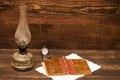pic of petroleum  - petroleum lamp old book and pocket watch over a vintage background - JPG