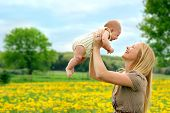 stock photo of country girl  - A happy young mother is smiling at her newborn baby girl as she lifts her up while outside in the country - JPG