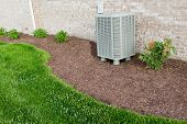 stock photo of manicured lawn  - Air conditioner condenser unit standing outdoors in a garden in a neat clean mulched flowerbed for easy access for maintenance - JPG