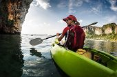 foto of kayak  - Young lady paddling the kayak in the calm bay with limestone mountains - JPG