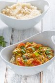 image of curry chicken  - chicken curry red pepper and coriander leaves with rice in a white bowl - JPG
