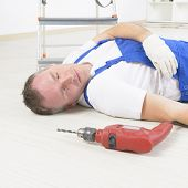 stock photo of workplace accident  - Man worker laying on a floor - JPG
