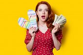 stock photo of redhead  - Surprised redhead girl in red polka dot dress with flip flops and money on yellow background - JPG
