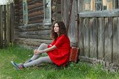 stock photo of old suitcase  - Young woman is sitting on threshold of old log house with vintage suitcase - JPG