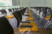stock photo of training room  - Many dark yellow chairs arranged neatly in a training room - JPG