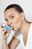 stock photo of inhalant  - Pretty girl using an asthma inhaler for preventing attacks - JPG