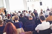 image of speaker  - Speaker Giving a Talk at Business Meeting. Audience in the conference hall. Business and Entrepreneurship. ** Note: Visible grain at 100%, best at smaller sizes - JPG