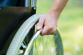 stock photo of wheelchair  - Detail of a man using a wheelchair in a park - JPG