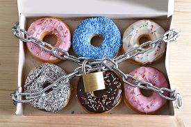 picture of addicted  - box full of tempting delicious donuts wrapped in metal chain and lock in sugar and sweet addiction and diet body and dental care concept - JPG