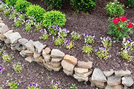 foto of rocking  - Natural rock retaining wall in a garden with rough rocks and stones arranged in a curve for a formal raised bed of flowering plants in a garden landscaping concept - JPG