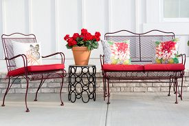image of spring-weather  - Colorful wrought iron garden furniture with vibrant red cushions and a red potted geranium standing on an open - JPG