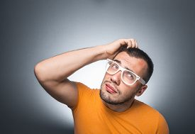 image of scrape  - Trendy guy scraped with his hand on head and thinking isolated on gray background studio shot - JPG