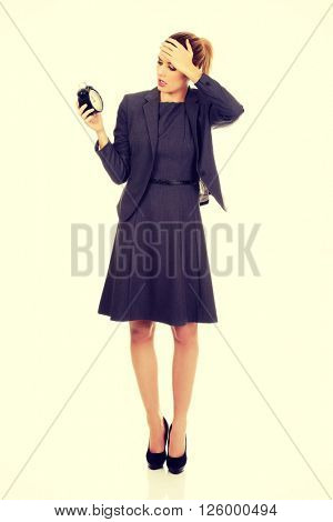 Worried business woman holding alarm clock