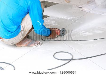Industrial tiler builder worker working with floor tile cutting equipment, with industrial concept, with industrial work, with industrial in house, with industrial in home, with industrial in city, with industrial people, with industrial object.