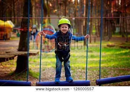 adventure climbing high wire park - kid on course in helmet and safety equipment.