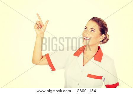 Smiling female doctor or nurse pointing at something