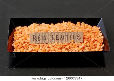 Red Lentils In The Black Plate With The Label On The Black Background
