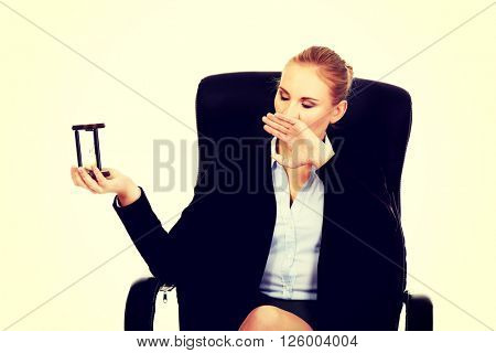 Yawning business woman holding a hourglass