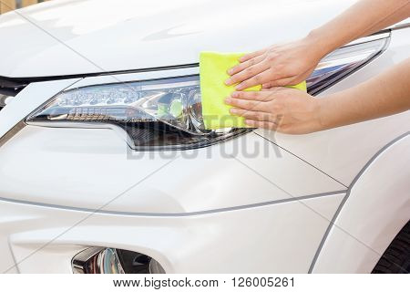 A woman hands with yellow microfiber cloth cleaning big white car, car concept, car idea, car housework, car cleaning , car washer.