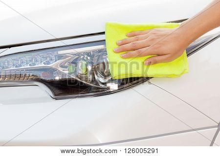Close up a woman hand with yellow microfiber cloth cleaning big white car, car concept, car idea, car housework, car cleaning , car washer.