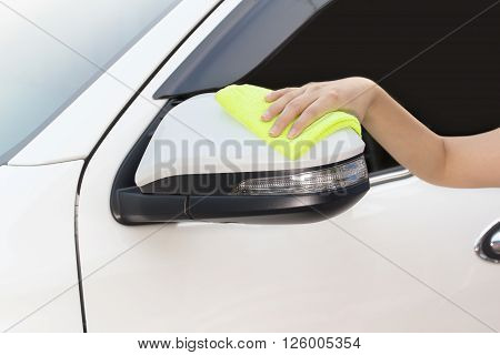 A woman hand with yellow microfiber cloth cleaning big white side mirror car, car concept, car idea, car housework, car cleaning , car washer.
