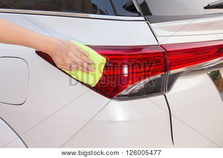 A woman hand with yellow microfiber cloth cleaning big white taillight car.