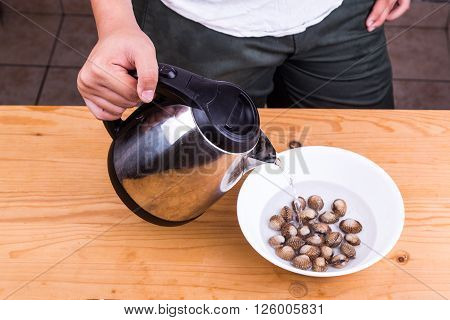 Person pouring boiling water over cockles in bowl as part of cooking preparation