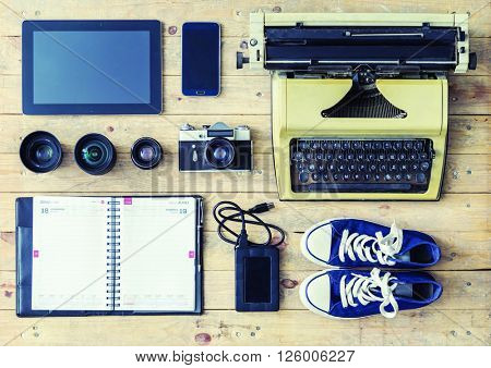 Journalistic equipment: typewriter, tablet, phone, camera, agenda, hdd storage, lenses and different objects. Freelancers outfit.