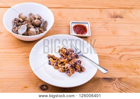 Boiled and prepared cockles with chili dip on wooden table.  It is a delicacy among Asians