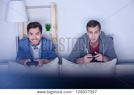 Handsome two men are playing video game at home. They are standing and leaning on the back of sofa. The man is smiling. His friend is looking at screen with disappointment