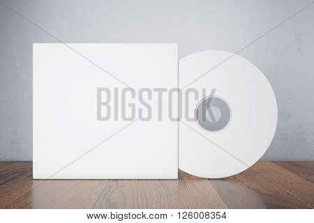 Blank white compact disk with cover on wooden table and concrete wall background. Mock up 3D Rendering