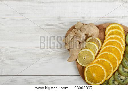 Slices of lemon, orange, kiwi and whole ginger arranged on a cutting board. Wooden board on right corner with copy space.