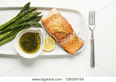 Roasted salmon fillet with asparagus on white