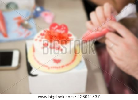 de-focused ; human hand try to made some cake