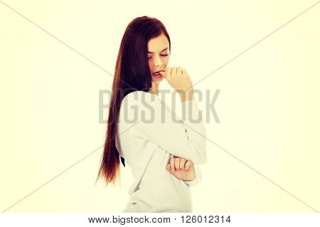 Sad lonely young woman biting her nail