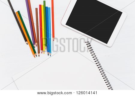 Colored pencils on wood table. Blank notebook and tablet. Wiew from above. Mockup
