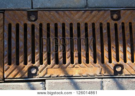 rusty metal grill with screws for sewerage
