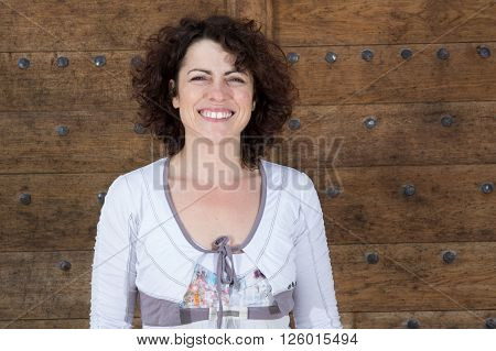 Smiling fashionable brunette laughs outdoors on wooden background