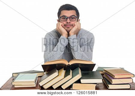 Young student in glasses sitting at a table reading a lot of books isolated on white