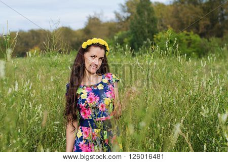 Beautiful woman with long hair and a wreath of flowers on his head walking in a field among the tall grass in warm summer evening