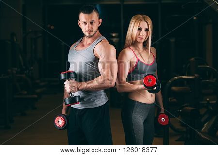 beautiful young sporty sexy couple showing muscle and workout in gym. dumbbell