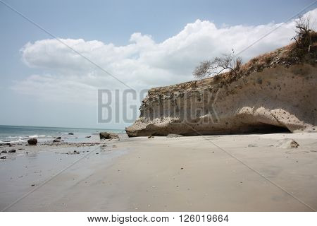 Blue water, clear skies, warm sand, and a rock formation on a Panamanian beach.