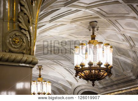 MOSCOW - MARCH 3: Chandelier in Prospekt Mira metro station on March 3, 2016 in Moscow. The ceiling vault is decorated with casts, and lighting comes from several cylindrical chandeliers.