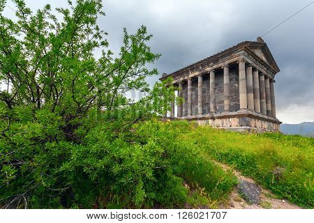 Hellenistic architecture the Pagan Temple of Garni (Armenia) in the green foliage of the tree.